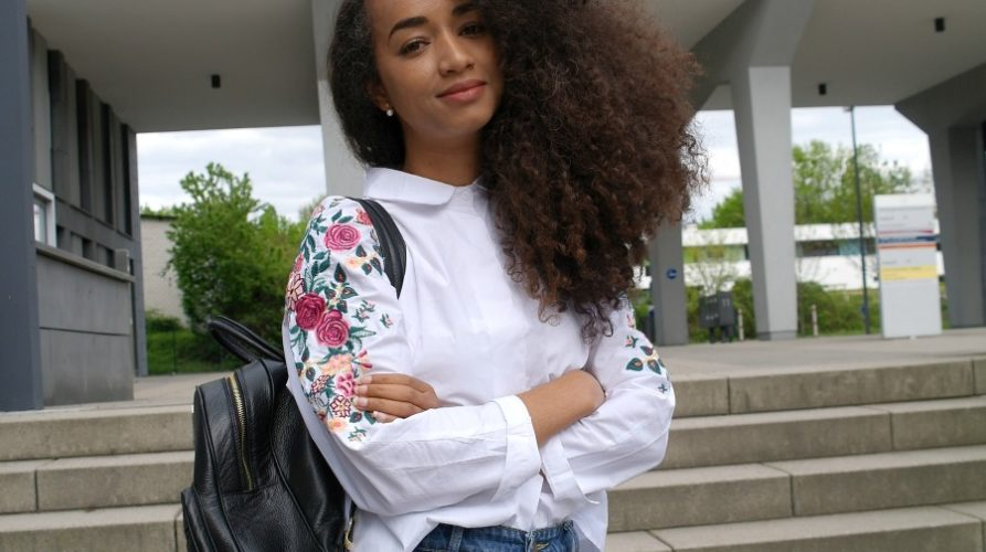 Outfit: Embroidered Flowers White Blouse and Mom Jeans with Ankle Boots and Black Backpack